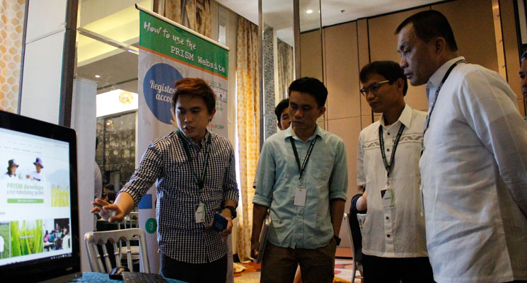 DA Assistant Secretary for Operations Federico Laciste Jr. and PRISM Project Leader Eduardo Jimmy Quilang from PhilRice take a tour of the PRISM website during the 2nd National Convention